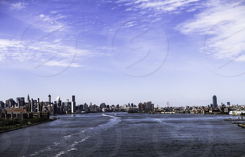city by body of water blue sky white clouds photo