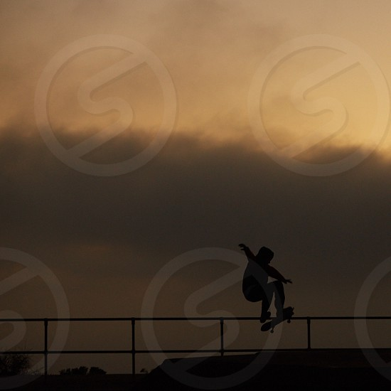 silhouette of person skating under  white sky during daytime photo