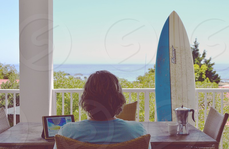 back of a person sitting in a chair with surfboard against patio rail overlooking water photo