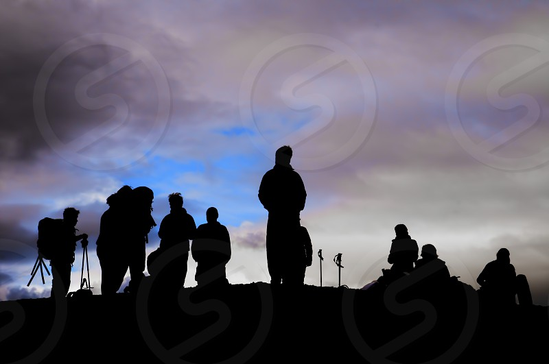 A group of trekkers black silhouette in the cloudy sky background in iceland photo