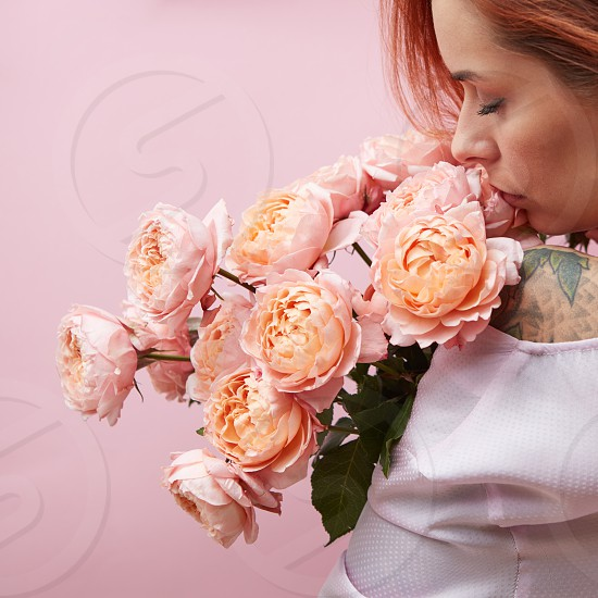 Woman with a tattoo holds on her shoulder a bouquet of pink Buttercup Asian on a pink background View from the back. Valentine's Day photo