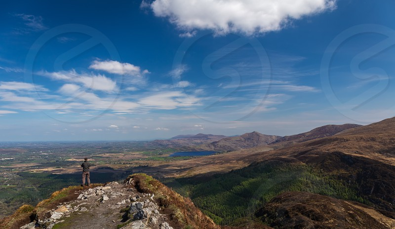 South and west of the town of Killarney in Co. Kerry is an expanse of rugged mountainous country. This includes the McGillycuddy's Reeks the highest mountain range in Ireland which rise to a height of over 1000 metres. At the foot of these mountains nestle the world famous lakes of Killarney. Killarney National Park . The distinctive combination of mountains lakes woods and waterfalls under ever changing skies gives the area a special scenic beauty. photo