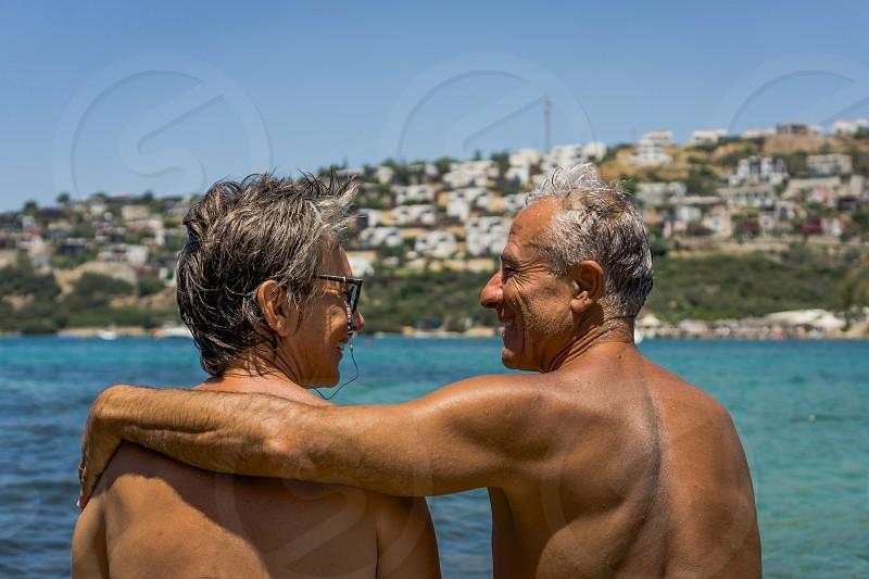 Happy senior couple by the sea enjoying retirement. Elderly couple hugging. Summet time. photo