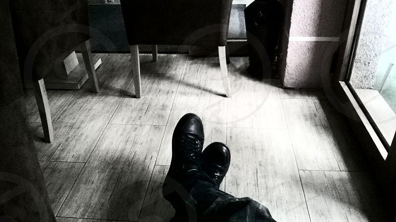 Black and white photo of crossed legs on a wooden floor in some interesting coffee place photo