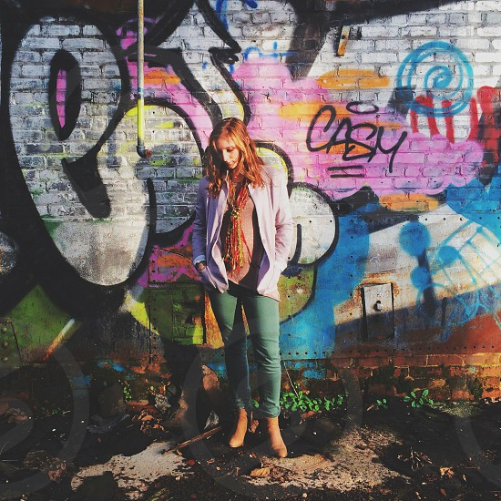 woman in olive skinny jeans and white cardigan near graffiti wall in floral scarf photo