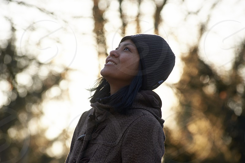 Side profile of an Asian woman in an autumn landscape basking in sunshine and feel happy and excited photo