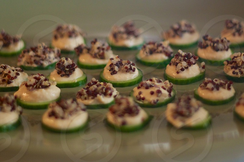 Cucumber slices topped with hummus and black quinoa photo