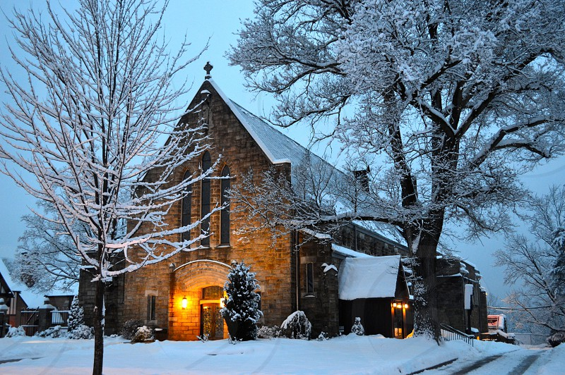 snow covered field and trees beside church photo