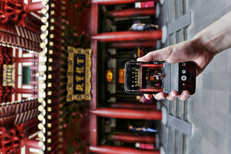 photographer holding phone taking picture of buddhist temple in chinatown Singapore photo