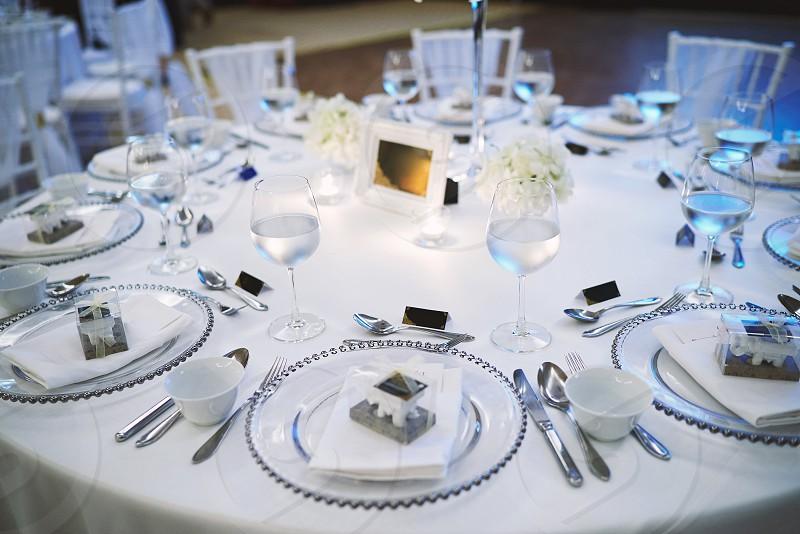 Luxury wedding reception dinner table setup  with silver dinnerware decoration photo