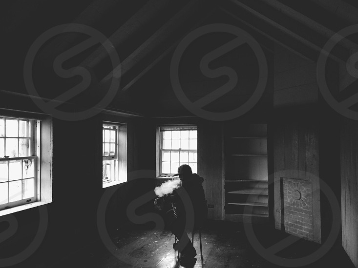 person blowing smoke from mouth sitting in room black and white photo photo