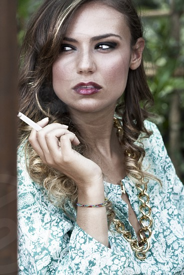 photo of woman wearing white and green floral keyhole long-sleeved top holding cigarette photo