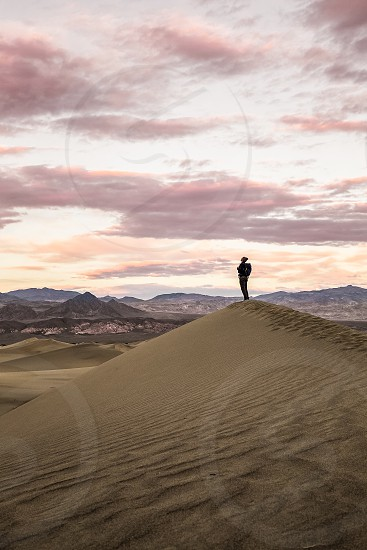 person standing in the middle of a desert surrounded by brown mountains photo