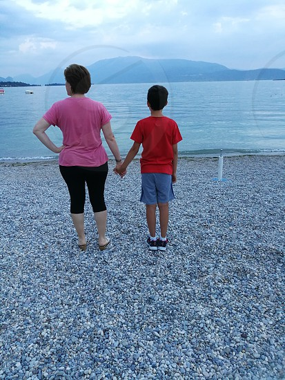 mother and son holding hands while sightseeing body of water during daytime photo