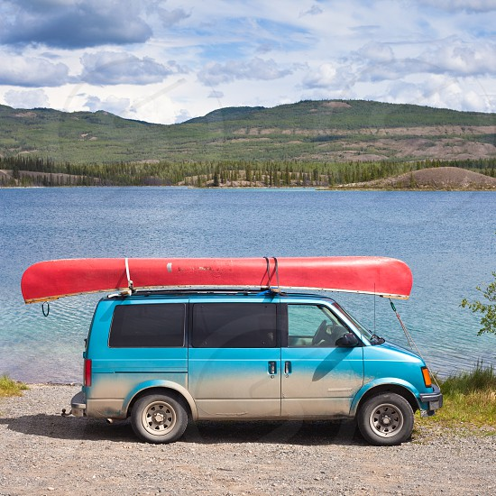 Dirty blue minivan with red canoe on roof-rack ready being put into water of Twin Lakes Yukon Territory Canada photo