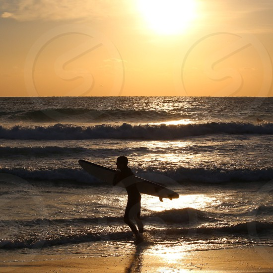 surfer carrying his surf board photo