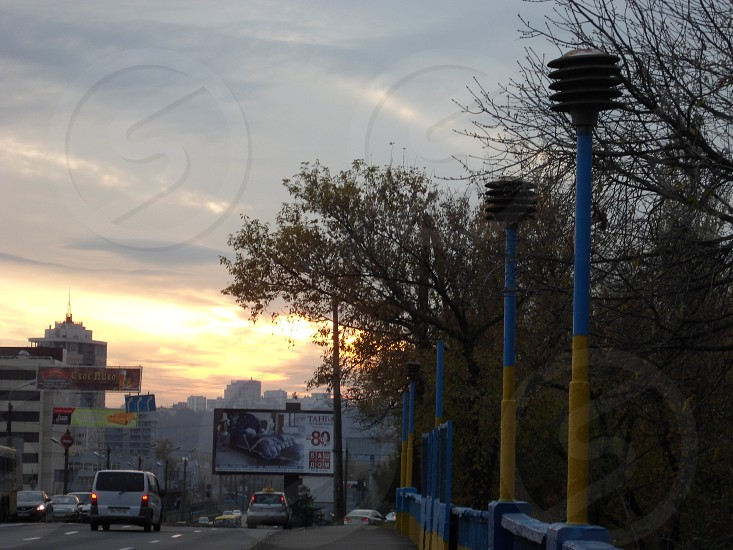 group of cars on top of gray pavement beside yellow and blue street lights during sunset photo