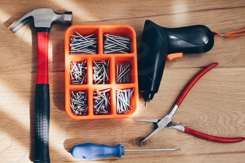 red handle pliers blue handle screwdriver red black and silver claw hammer and orange plastic case with nails photo
