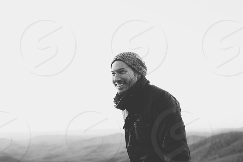 grayscale photography of a man wearing jacket and knit cap near foggy mountain photo