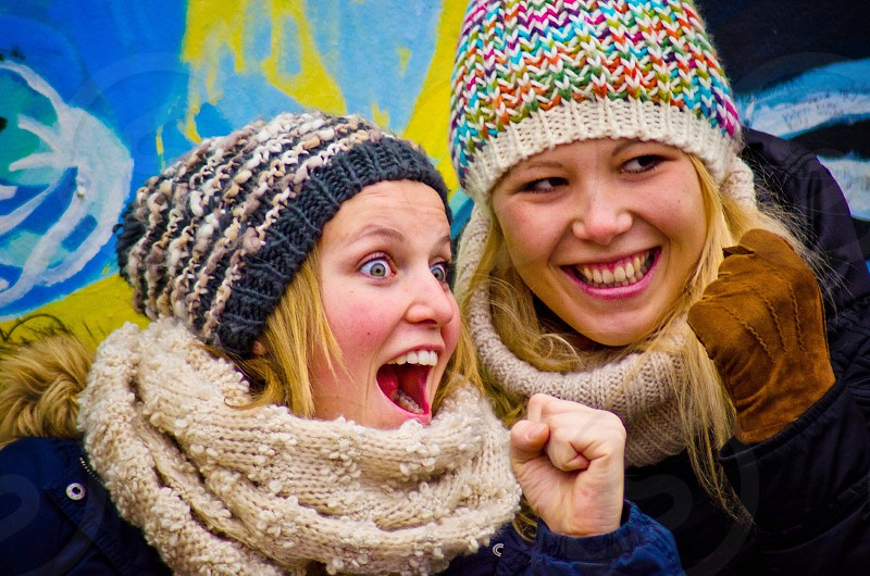 woman in blue and white beanie and woman in multicolored beanie photo