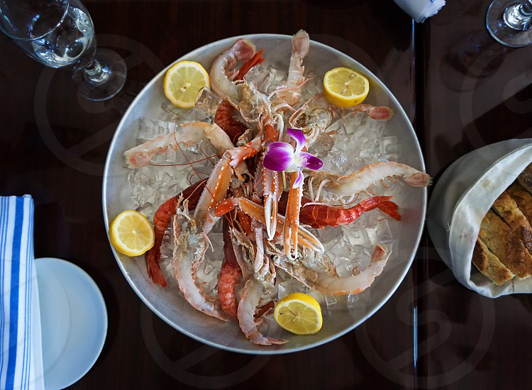 shrimp salad with ice on round plate on dining table photo