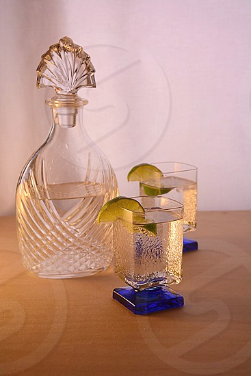 Clean minimal set-up Elegant decanter and glassware gin and tonic's with lime wedges. photo