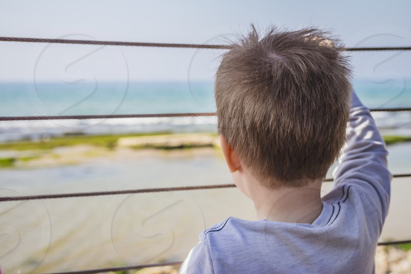 Young boy looks far away to the horizon from behind metal fence. photo