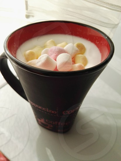black and red ceramic cup with marshmallows photo