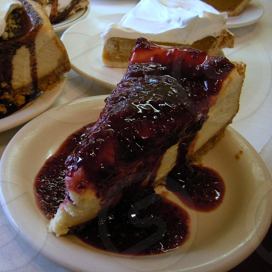 Cheesecake with raspberry sauce on white plate in front of pie slices photo
