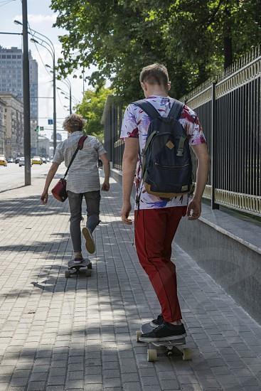 Two friends skateboard riders moving along the pedestrian walkway view from behind photo