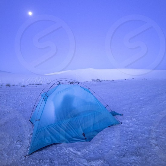 blue dome tent on the snow under purple sky photo