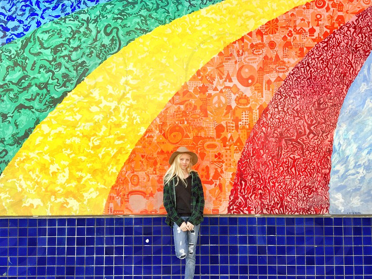 Young girl standing in front of a rainbow wall mural in San Francisco California photo
