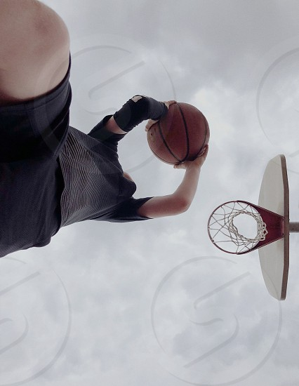 A boy jumping to a basketball hoop.  photo