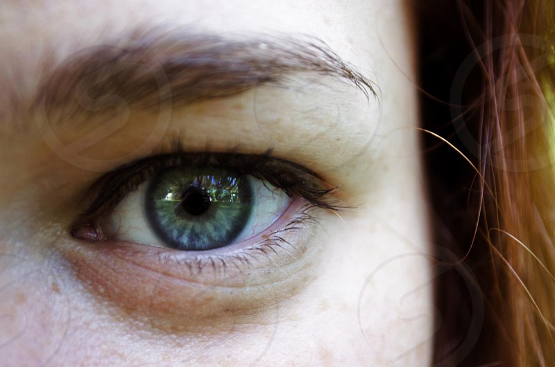 women's left eye with brown hair during daytime photo