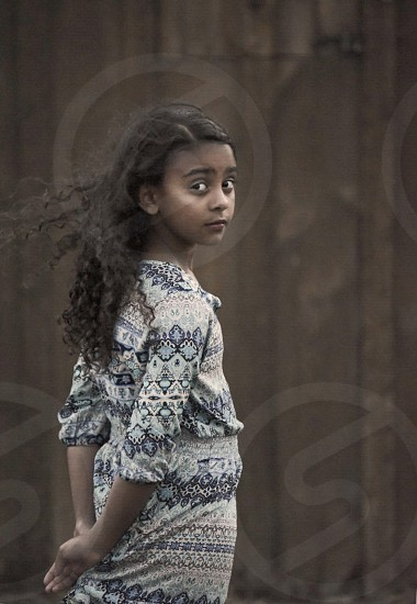 girl in grey blue and brown tribal elbow sleeve dress standing with hands on back and hair fluttering near wooden wall photo