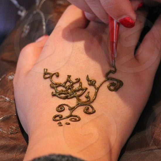 Looking down at a female hand being painted with a ahenna design photo