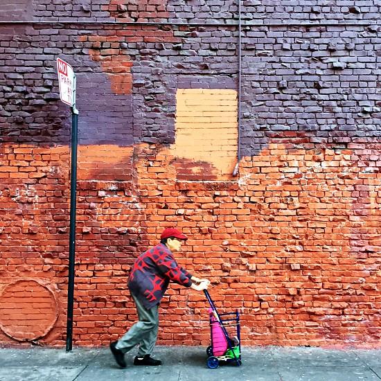 Older woman shopping cart brick wall photo
