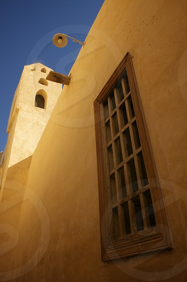 Building within the confines of the Monastery of St. Anthony near Hurghada Egypt. monasticism christianity monks adobe yellow blue tower bell early light beautiful photo