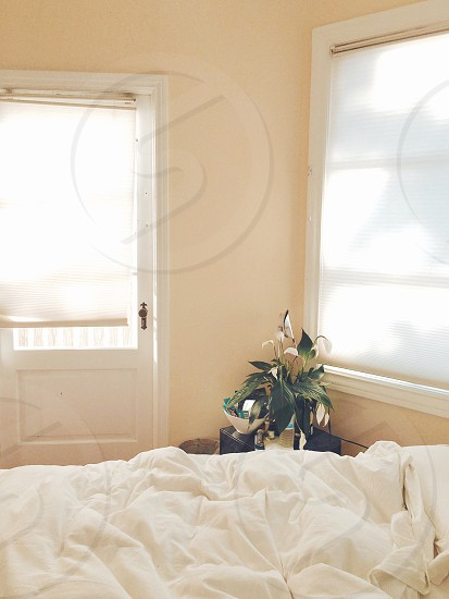 white blanket on bed beside window during daytime photo