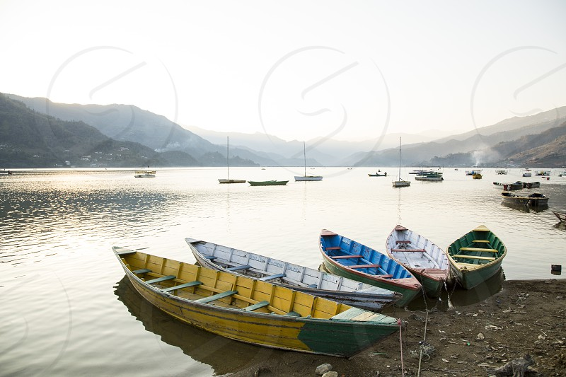 Colorful boats on Phewa Lake in Pokhora Nepal at sunset. photo