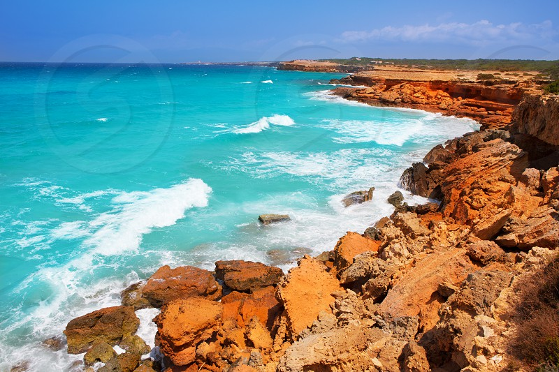 Cala Saona rocky coast with aqua turquoise rough Mediterranean sea photo