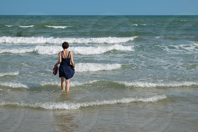 young woman with short hair walking into ocean wearing dress and holding shoes photo