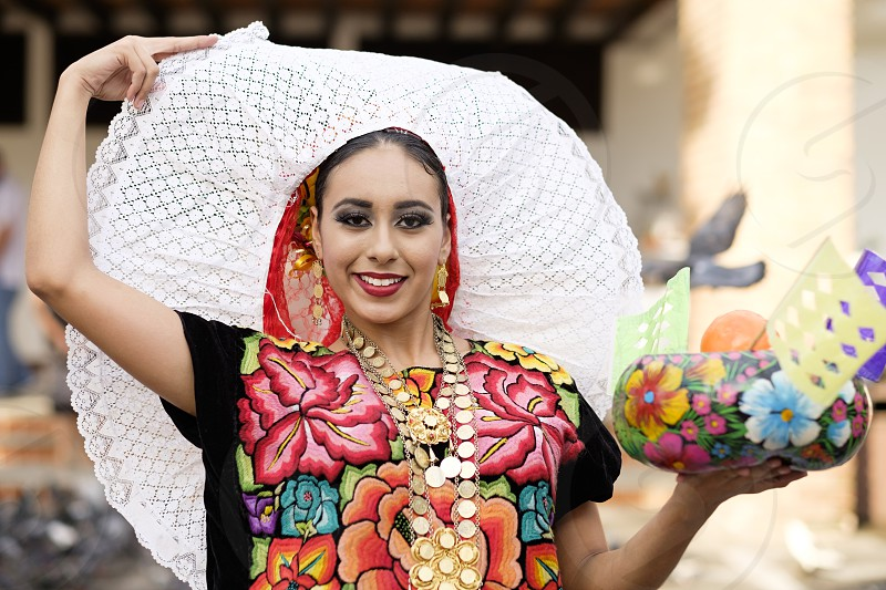 Young Mexican woman in folkloristic outfit. Puerto Vallarta Jalisco Mexico. Xiutla Dancers - a folkloristic Mexican dance group in traditional costumes representing the culture and different regions of Mexico. photo