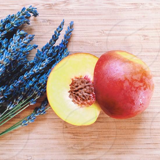 fresh nectarine cut in half next to bundle of lavender photo