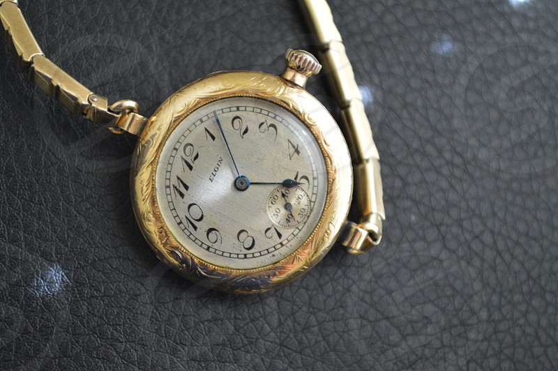 gold pocket watch showing 5:7 time photo