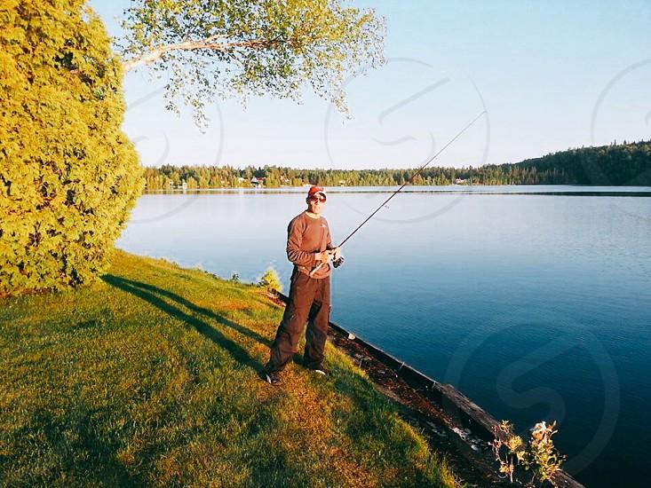 man holding fishing rod near lake under blue sky at daytime photo