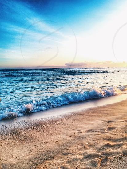 brown sand beach beside clear blue ocean during daytime photo