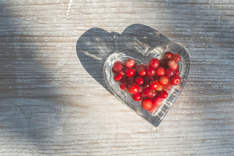 Raspberries in a bowl on wood. Heart shape bowl. photo