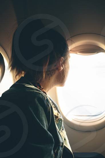 woman in jean jacket looking out airplane window photo