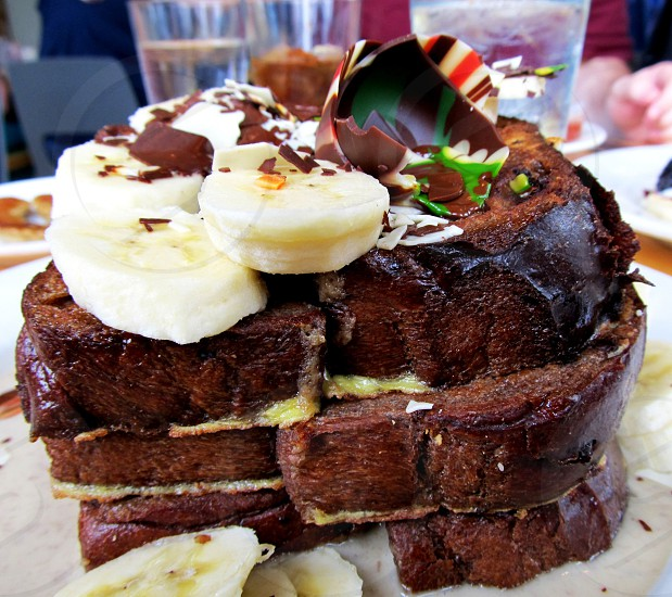 Chocolate French toast stack with broken chocolate shell and banana slices photo